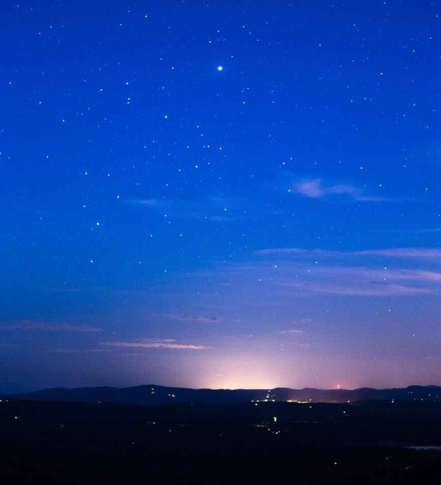 silhouette of mountain range under stars